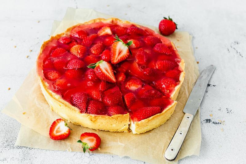 Erdbeerkuchen in Herzform auf weißem Untergrund mit angestellten Erdbeeren