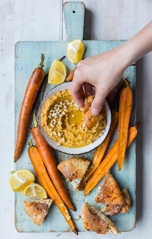 Schale mit Kürbis-Hummus mit angelegten Möhren und Pita-Chips