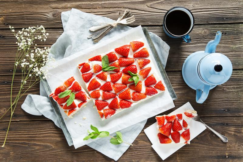 Erdbeer-Schmand-Kuchen aus dem Thermomix® auf dunklem Holztisch.