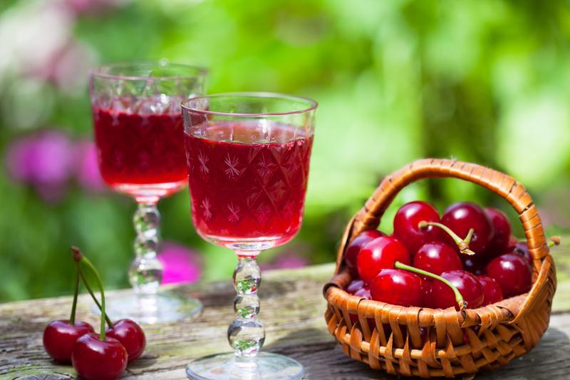 Zwei Gläser mit Kirschlikör mit angestelltem Körbchen mit Kirschen auf Tisch mit Garten im Hintergrund