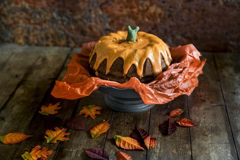 Kuchen-Kürbis mit Papier unterlegt auf einer Kuchenplatte.