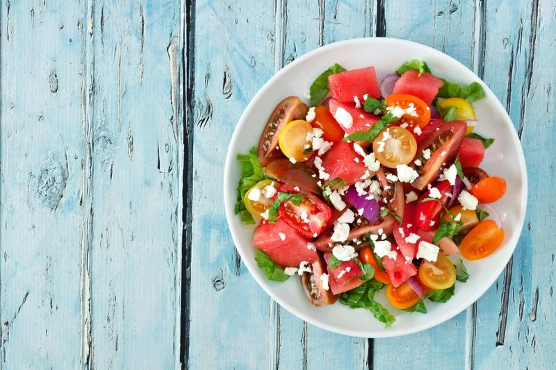 Große weiße Schüssel mit Wassermelonen-Feta-Salat aus dem Thermomix® auf hellblauem Holzuntergrund