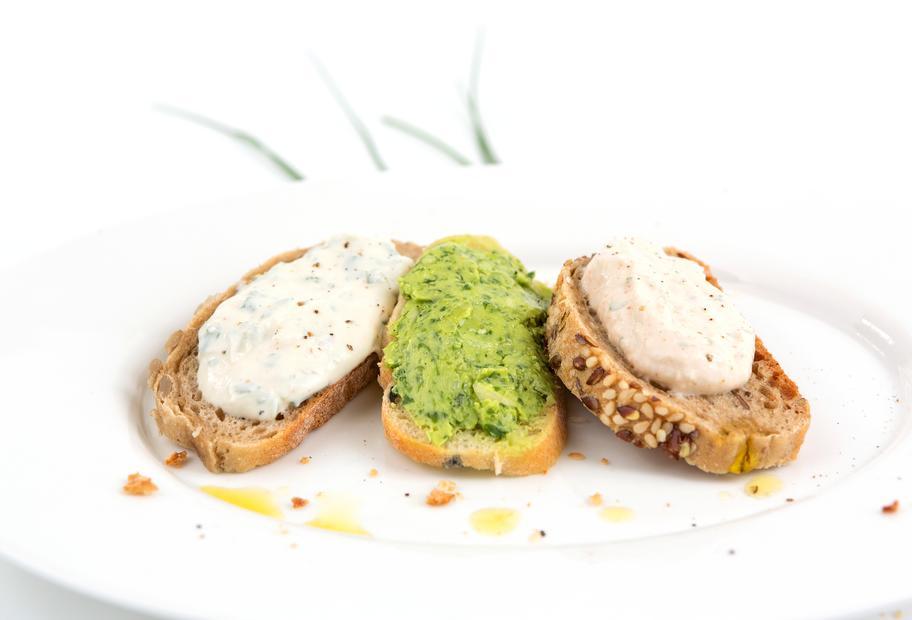 Drei Scheiben Baguette mit verschiedenem Quark bestrichen